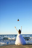 Bride throwing bouquet in sea Royalty Free Stock Photography