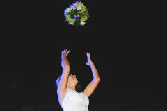 Bride Throwing Bouquet. Bride throwing wedding bouquet in night sky Royalty Free Stock Photography