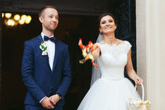 Bride throws sweets standing with a groom in the church entrance.  Stock Photos