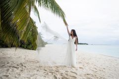 The bride throws a white dress in the air. Wedding on a tropical island royalty free stock photo