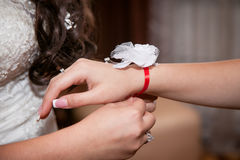 Bride ties his girlfriend decoration of flowers on hand Royalty Free Stock Images