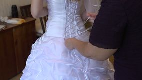 Bride to tie Dress. Bridesmaid tying bow on wedding dress in room bride stock video