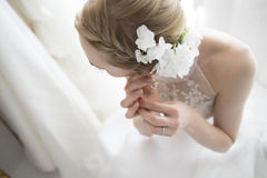 Bride to try to remove the earrings Stock Images
