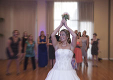 Bride tossing bouquet. A bride throwing her bouquet during her reception Stock Photos