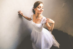 Bride touches her shoulder delicately standing with closed eyes Royalty Free Stock Image