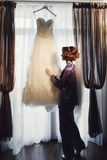 Bride touches a wedding dress before putting it on Royalty Free Stock Photo