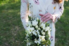 Bride touching wedding bouquet with one hand with wedding ring on her finger. Wedding details Royalty Free Stock Images