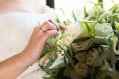 Bride touching wedding bouquet with one hand with wedding ring on her finger. Wedding details Stock Photos