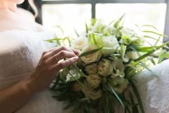 Bride touching wedding bouquet with one hand with wedding ring on her finger.  details. Bride touching wedding bouquet with one hand with wedding ring on her Royalty Free Stock Photos