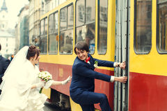 Bride tries to catch a groom who climbs on a tram Stock Photography