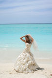 Bride on tropical beach. Attractive young bride in white wedding dress on tropical beach in Maldives, catamaran in blue sea Stock Photography