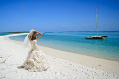 Bride on tropical beach. Attractive young bride in white wedding dress on tropical beach in Maldives, catamaran in blue sea Stock Images