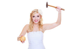 Bride trying to break piggy bank with hammer Stock Photo