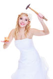 Bride trying to break piggy bank with hammer Royalty Free Stock Photography