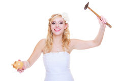 Bride trying to break piggy bank with hammer Royalty Free Stock Photos