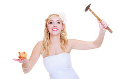 Bride trying to break piggy bank with hammer Royalty Free Stock Image