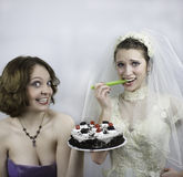 Bride trying to diet is tempted by bridesmaid Stock Images