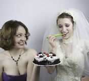 Bride trying to diet is tempted by bridesmaid Stock Photo