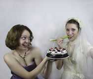 Bride trying to diet is tempted by bridesmaid Stock Photos