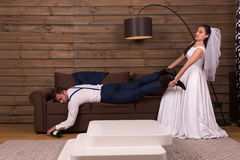 Bride is trying to wake up a drunk sleeping groom Stock Photography