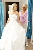 Bride trying on wedding dress with sales assistant Royalty Free Stock Images