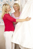 Bride trying on wedding dress with sales assistant Stock Image