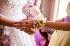 Bride tying bridemaids wrist corsage Royalty Free Stock Photo