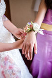 Bride tying bridemaids wrist corsage Royalty Free Stock Images