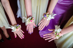Bride tying bridemaids wrist corsage Royalty Free Stock Image