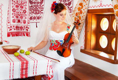 Bride in the ukrainian style is holding the violin. Royalty Free Stock Image