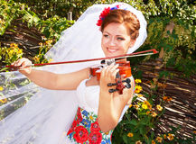Bride in the ukrainian style is playing the violin. Stock Photos
