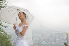 Bride with umbrella Stock Images
