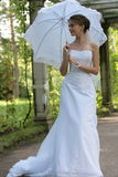 Bride and umbrella. The smiling bride in a white dress with an umbrella in park Royalty Free Stock Images