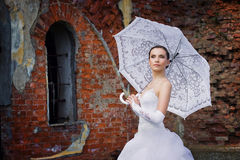 A bride with an umbrella against brick wall Stock Images