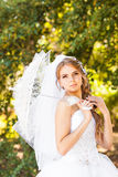 Bride with umbrella. Standing near tree. Wedding day Stock Images