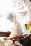 Bride under veil is sitting on the chair Royalty Free Stock Photos
