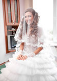 Bride under white veil sitting in appartment Royalty Free Stock Image
