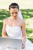 Bride using laptop in garden Royalty Free Stock Images