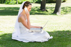 Bride using laptop and mobile phone in park Royalty Free Stock Images