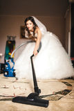 The bride vacuums a carpet in the room Stock Photo