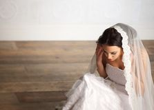 Bride and Veil. Elegant bride sitting on the floor with veil over her head Royalty Free Stock Photos