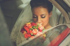 Bride in veil with bouquet sitting in car Royalty Free Stock Images