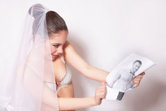 Bride in veil break the groom photo, gray background Royalty Free Stock Images