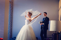 The bride with veil and groom in interior of hotel Royalty Free Stock Photos