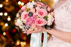 The bride in a veil holds a beautiful bouquet of delicate roses. The lights in the background. French manicure on nails. women`s. The bride in a veil holds a stock photo
