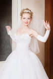 A bride with a veil at home. A bride with a veil looks playfully stock photography