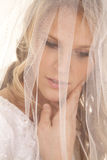 Bride with veil over face close look down. A bride has a veil over her face with a serious expression Stock Image