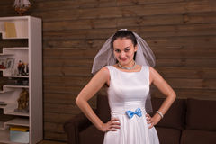 Bride in veil and white dress with blue bow posing Royalty Free Stock Images
