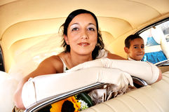 Bride in a vintage car. Bride and son inside an antique and elegant car. They go to the church Stock Image
