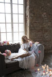 Bride on vintage sofa with flowers and candles Royalty Free Stock Photos